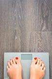 Pomaga gubić kilo z kobieta ciekami kroczy na ciężar skala Fotografia Stock