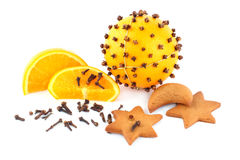 Pomander and gingerbreads in the form of stars. Fresh orange and clove in the form of pomander attached to the gold string with cakes and slice of orange stock images