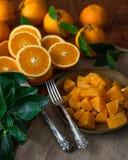 Pomarańcze plasterki i pomarańcze liście na kuchennym stole zdjęcia royalty free