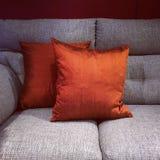 Pomarańcz poduszki na szarej kanapie Fotografia Royalty Free