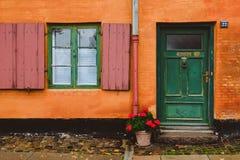 Pomarańcze ściana, Zielony Windows i Czerwony kwiatu garnek, Obraz Royalty Free