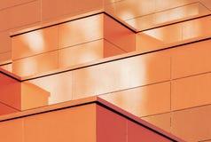 Pomarańcze barwił geometrycznego tło metalu budynku fasada zdjęcie royalty free