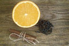 Pomarańcze, Cynamonowi kije, cloves na drewnianym tle obrazy stock
