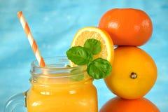 Pomarańcze, cytryna, mandarynka i koloru żółtego sok w szklanym słoju, obraz stock