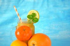 Pomarańcze, cytryna, mandarynka i koloru żółtego sok w szklanym słoju, obraz royalty free