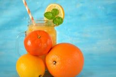 Pomarańcze, cytryna, mandarynka i koloru żółtego sok w szklanym słoju na błękitnym tle, zdjęcia stock