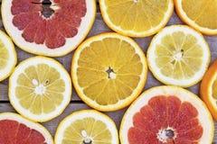 Pomarańcze, grapefruitowych i cytryny plasterki na drewnianym tle, obrazy royalty free
