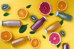Pomarańcze, grapefruits i różni soki na żółtym tle, poj?cie zdrowy zdjęcie stock