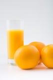 Pomarańcze i glassful owocowy sok obraz stock