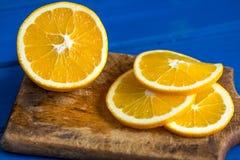 Pomarańcze i pomarańcze plasterki na błękitnym tle Fotografia Royalty Free