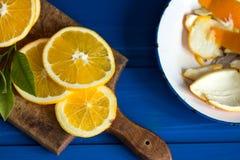 Pomarańcze i pomarańcze plasterki na błękitnym tle Obraz Stock