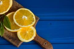 Pomarańcze i pomarańcze plasterki na błękitnym tle Obrazy Stock