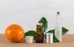 Pomarańcze Istotna Nafciana butelka Z Białą nakrętką, cytrusów liśćmi i Rolkową butelką, Obrazy Stock