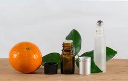 Pomarańcze Istotna Nafciana butelka Z Czarną nakrętką, cytrusów liśćmi i Rolkową butelką, Obrazy Royalty Free