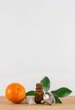 Pomarańcze Istotna Nafciana butelka Z nakrętką, cytrusów liśćmi i lejem Białymi, Zdjęcie Stock