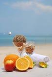 Pomarańcze, jabłko, sunglass i ręka ręcznik na plaży, Zdjęcia Royalty Free