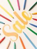Pomarańcze malował literowanie sprzedaż na białym tle między markierami Zdjęcia Stock