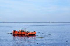 Pomarańcze malująca metal barka zakotwiczał wzdłuż ocean zatoki zdjęcie stock