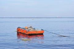 Pomarańcze malująca metal barka zakotwiczał wzdłuż ocean zatoki obraz stock