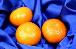 Pomarańcze na jedwabniczej błękitnej tkaninie Zdjęcie Stock