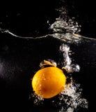 Pomarańcze pod wodą na czarnym tle fotografia stock