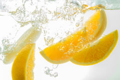 Pomarańcze Pokrajać spadać głęboko pod wodą z dużym pluśnięciem Fotografia Stock