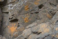 Pomarańcze ręki błotniści druki na kamiennej ścianie Obrazy Royalty Free