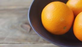 Pomarańcze są jaskrawym pomarańcze w popielatym pucharze na starym drewnianym tła zbliżeniu Zdjęcia Royalty Free