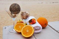Pomarańcze, sunglass i ręka ręcznik na plaży, Fotografia Royalty Free