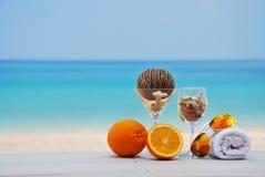 Pomarańcze, sunglass i ręka ręcznik na plaży, Zdjęcia Stock