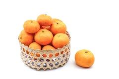 Pomarańcze w bambusowym koszu odizolowywającym na bielu Obrazy Stock