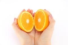 Pomarańcze w cięciu w jego ręki obraz royalty free