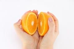 Pomarańcze w cięciu w rękach dziewczyna zdjęcia royalty free