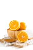 Pomarańcze w drewnianym pucharze na bielu obraz stock
