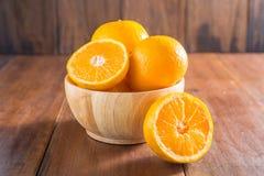 Pomarańcze w drewnianym pucharze na drewnianym tle zdjęcia stock