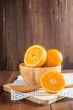 Pomarańcze w drewnianym pucharze na drewnianym tle obraz stock