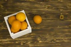 Pomarańcze w pudełku na drewnianym tle Obrazy Royalty Free