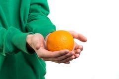 Pomarańcze w rękach mężczyzna w zielonym hoodie zbliżeniu przeciw białemu tłu Ludzie i karmowy pojęcie obraz royalty free