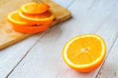 Pomarańcze z kawałkami na tnącej desce Fotografia Royalty Free