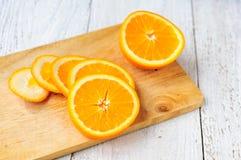 Pomarańcze z kawałkami na tnącej desce Zdjęcie Royalty Free