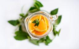 Pomarańcze z mennicą przy smoothies filiżanką Zdjęcia Royalty Free