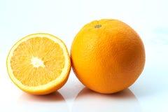 Pomarańcze z połówką na bielu Zdjęcia Royalty Free