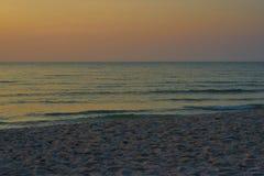 Pomarańcze, zmierzch, wzrosta niebo, fala lub piasek na plażowym widoku, zdjęcia stock