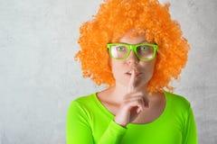 Pomarańczowa dziewczyna z palcem na wargach fotografia royalty free