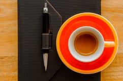 Pomarańczowa filiżanka kawa espresso kawowy czarny organizator z piórem fotografia stock