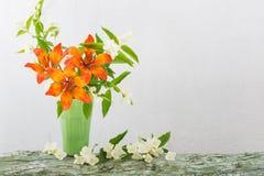 Pomarańczowa leluja w wazie na białym tle fotografia royalty free