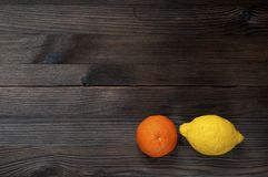 Pomarańczowa mandarynka i kolor żółty cytryna na ciemnym nieociosanym drewnianym tle Obrazy Royalty Free