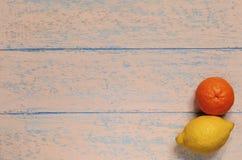 Pomarańczowa mandarynka i kolor żółty cytryna na podławym starym drewnianym tle Zdjęcia Stock