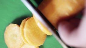 Pomarańczowa marchewka dostaje pokrajać z dużym ostrym nożem na zielonym kuchennym stole zbiory
