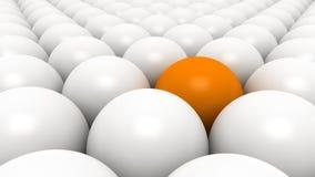 Pomarańczowa piłka między białymi piłkami Fotografia Royalty Free